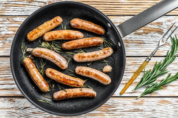 Embutidos caseros fritos en sartén, carne de res y cerdo. mesa de madera. vista superior.