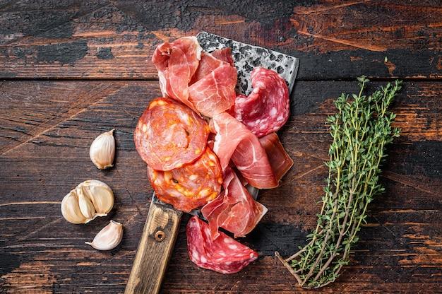 Embutidos españoles salami, jamón, choriso, salchichas curadas en un cuchillo de carnicero. fondo de madera oscura. vista superior.