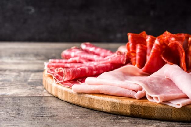 Embutidos en tabla de cortar en mesa de madera jamón, salami, salchicha, mortadela y pavo