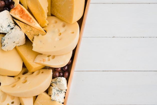 Emmental; azul; queso cheddar con aceitunas en bandeja en escritorio blanco