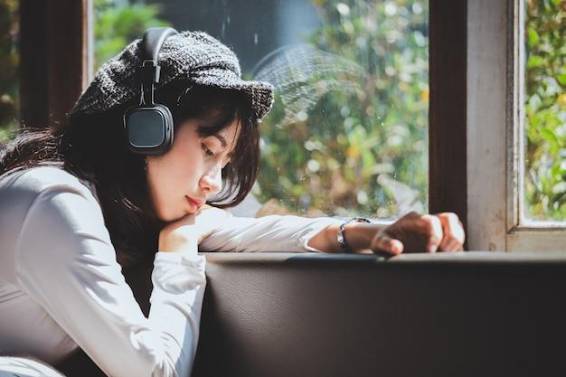 Emoción de una chica joven triste escuchando música mirando por la ventana