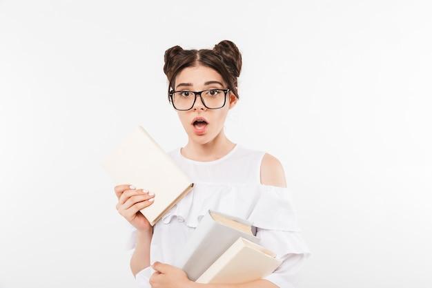 Emocionada adolescente con peinado de bollos dobles y aparatos dentales que expresan perplejidad mientras sostiene muchos libros de estudio, aislado en blanco
