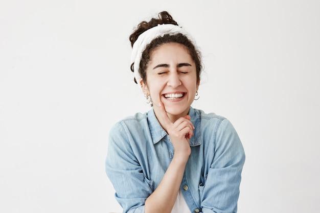 Emocionada, alegre, feliz mujer morena con los ojos cerrados, tiene una expresión soñadora, piensa en algo agradable, sueña con relaciones perfectas. expresión facial positiva, emociones y sentimientos.