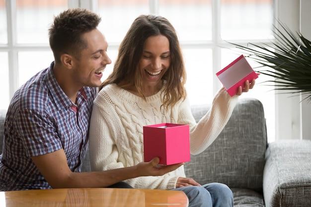 Emocionada apertura de caja de regalo de apertura de mujer joven presente de marido