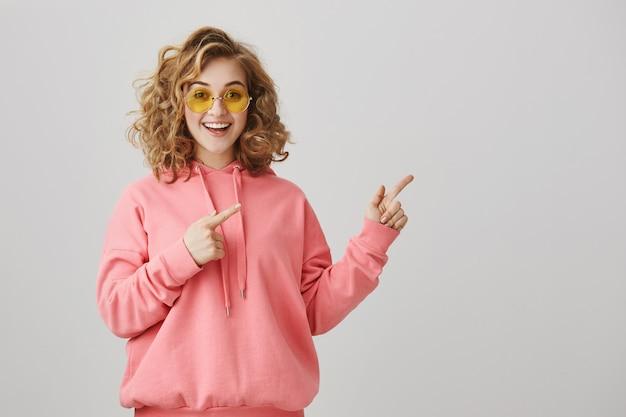 Emocionada chica de pelo rizado con estilo en gafas de sol apuntando a la derecha, mostrando el camino
