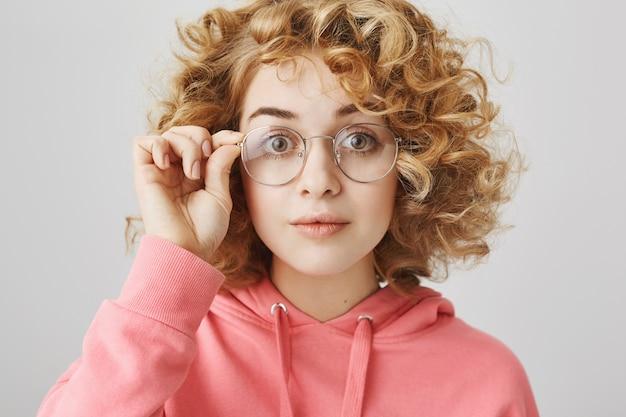 Emocionada chica de pelo rizado mirando interesada en gafas