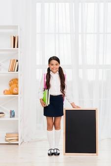 Emocionada colegiala hispana con cuadernos y pizarra.