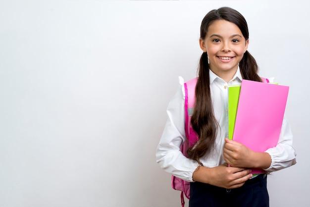 Emocionada colegiala hispana portando cuadernos.