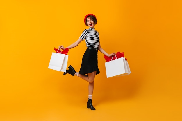 Emocionada dama morena bailando con bolsas de tienda