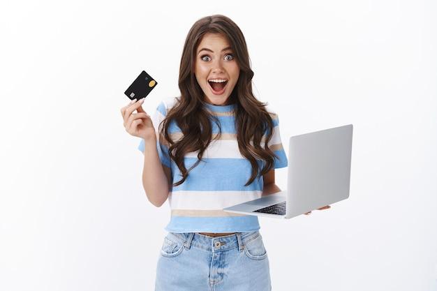 Emocionada, divertida, atractiva mujer sostiene una computadora portátil y una tarjeta de crédito, sonriendo fascinada, lista para pagar la compra, navegando por internet comprando dispositivos en línea, adora lo fácil que es comprar con su banco