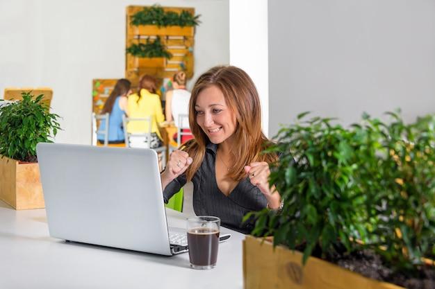Emocionada empresaria feliz con los brazos levantados, sentado a la mesa con la computadora portátil celebrando su éxito