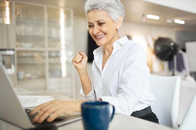 Emocionada empresaria de mediana edad elegante usando la computadora portátil para el trabajo, apretando los puños, feliz de ganar licitación