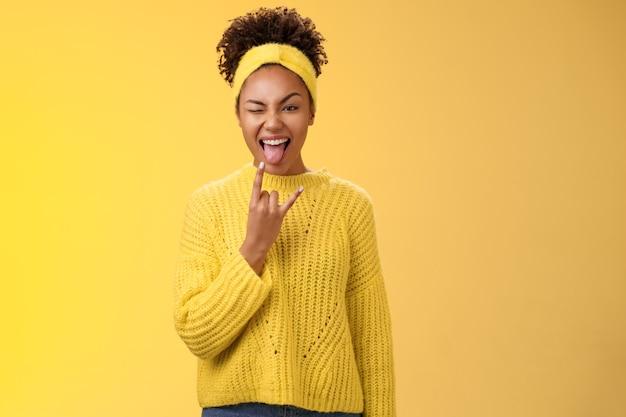Emocionada encantadora sonriente atrevida descarada joven afroamericana divirtiéndose mostrar lengua rock-n-roll gesto de heavy metal guiñando un ojo feliz disfrutando de una fiesta increíble, de pie sobre fondo amarillo.