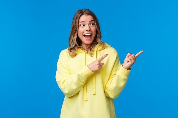 Emocionada feliz, alegre mujer caucásica con una sonrisa blanca y radiante, usar una sudadera con capucha amarilla, reaccionar emocionado y divertido ante noticias increíbles, pancarta genial, señalar con el dedo a la derecha, mirar hacia otro lado, pared azul