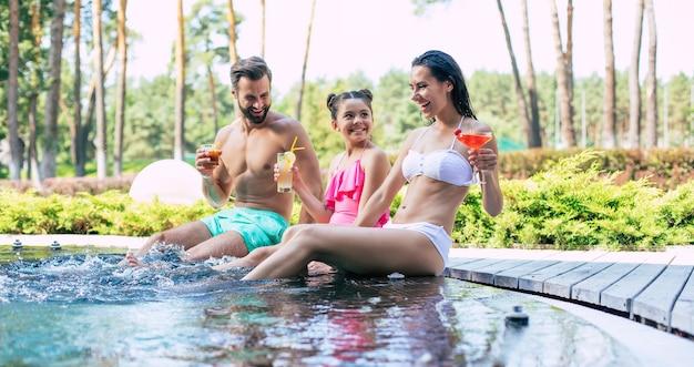 Emocionada feliz familia joven hermosa moderna en la piscina de verano durante unas vacaciones en el hotel se divierten y beben algunos cócteles.