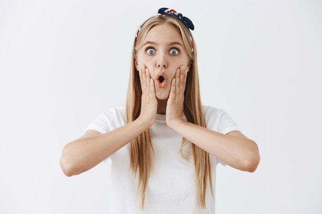 Emocionada feliz joven rubia posando contra la pared blanca