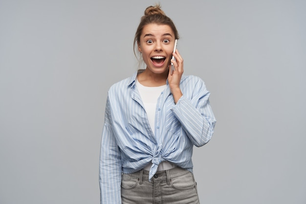 Emocionada, feliz mujer con cabello rubio recogido en un moño. vistiendo camisa anudada a rayas y hablando por su teléfono celular. escuche buenas noticias. mirando a la cámara, aislada sobre pared gris