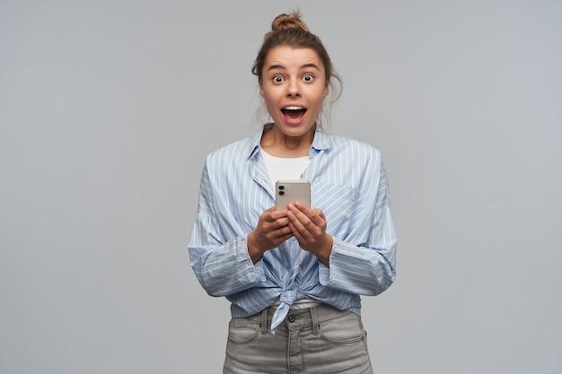Emocionada, feliz mujer con cabello rubio recogido en un moño. vistiendo una camisa anudada a rayas y sosteniendo un teléfono inteligente. tengo una gran noticia. mirando a la cámara, aislada sobre pared gris
