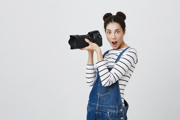 Emocionada fotógrafa creativa tomando fotografías en la cámara, mirando divertido mientras fotografía