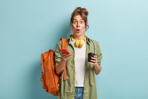 Emocionada hermosa chica hipster abre la boca de la sorpresa, lee noticias en internet, usa un teléfono celular moderno y auriculares para escuchar música o audiolibros, toma café para llevar, asiste a clases
