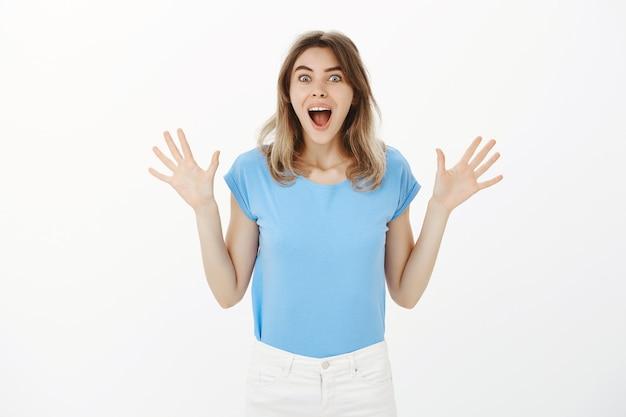 Emocionada hermosa mujer rubia contando buenas noticias, regocijándose y celebrando