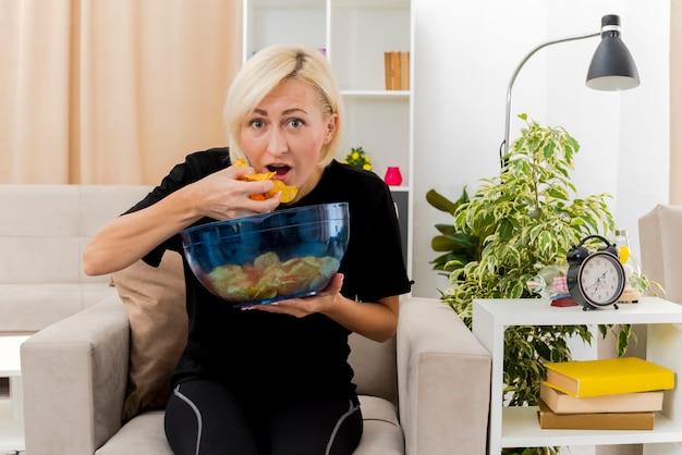 Emocionada hermosa mujer rusa rubia sentada en un sillón sosteniendo y comiendo un tazón de patatas fritas dentro de la sala de estar
