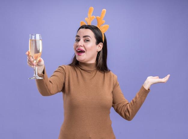 Emocionada joven hermosa niña vistiendo un suéter marrón con aro de pelo de navidad sosteniendo una copa de champán extendiendo la mano aislada sobre fondo azul.
