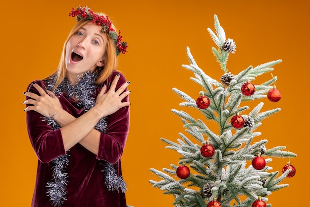 Emocionada joven hermosa de pie cerca del árbol de navidad con vestido rojo y corona con guirnalda en el cuello poniendo las manos en el hombro aislado sobre fondo naranja