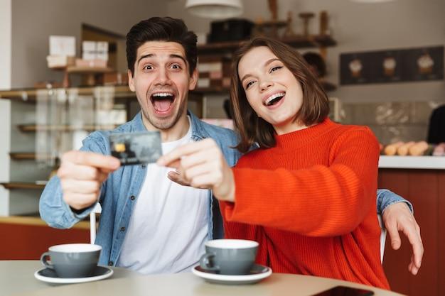 Emocionada joven pareja sentada en la mesa de café