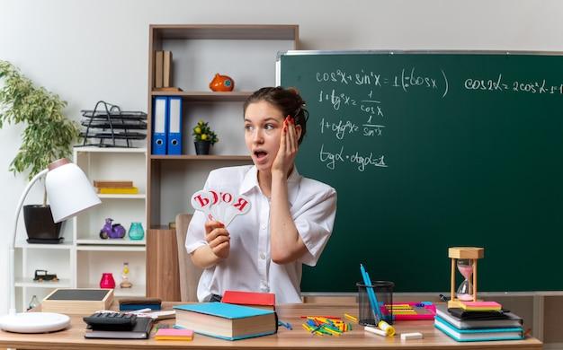 Emocionada joven profesora de matemáticas sentada en el escritorio con útiles escolares sosteniendo la letra del alfabeto ruso ventiladores mirando a un lado manteniendo la mano en la cara en el aula