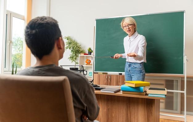 Emocionada joven profesora rubia con gafas en el aula de pie frente a la pizarra sosteniendo un puntero mirando sentado estudiante adolescente chico mostrando la mano vacía