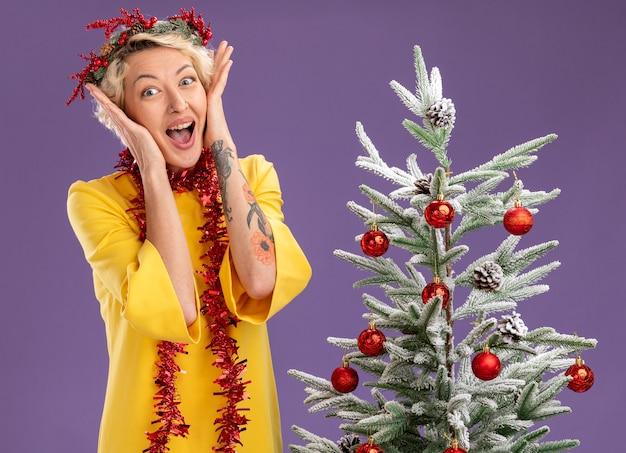 Emocionada joven rubia con corona de navidad y guirnalda de oropel alrededor del cuello de pie cerca del árbol de navidad decorado manteniendo las manos en la cara mirando a cámara aislada sobre fondo púrpura