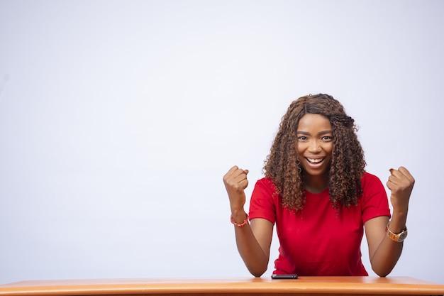 Emocionada joven sentada en un escritorio y celebrando, frente a un fondo blanco.