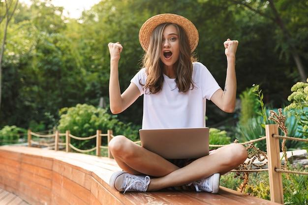 Emocionada joven sentada con ordenador portátil en el parque al aire libre