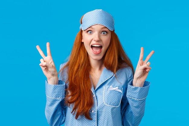 Emocionada linda pelirroja en máscara para dormir y pijama mostrando signos de paz y gritando