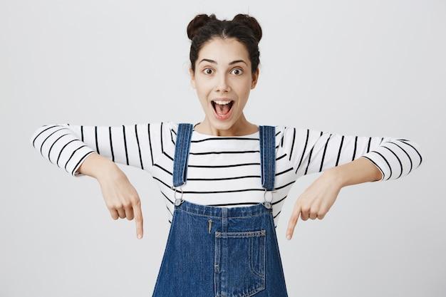 Emocionada mujer adolescente jadeando, apuntando hacia abajo