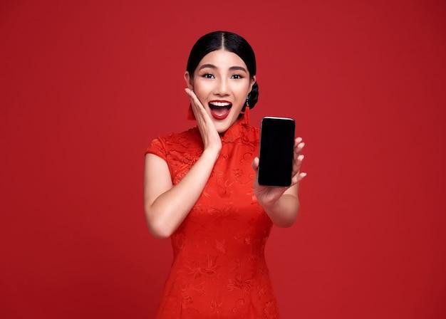 Emocionada mujer asiática con vestido tradicional cheongsam qipao mostrando teléfono móvil aislado en la pared roja.
