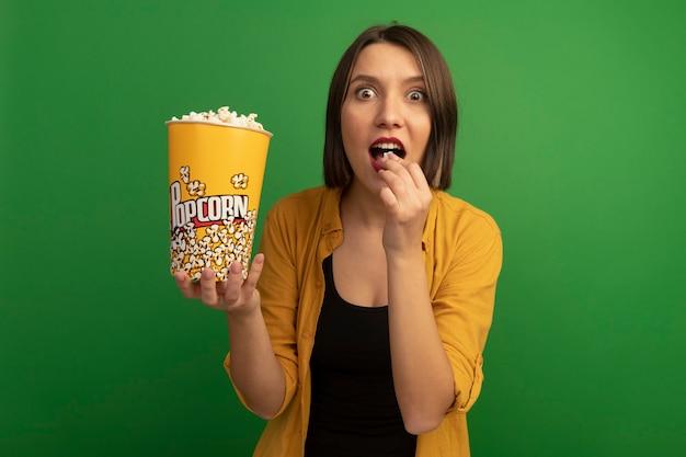 Emocionada mujer bonita caucásica come y sostiene un cubo de palomitas de maíz en verde