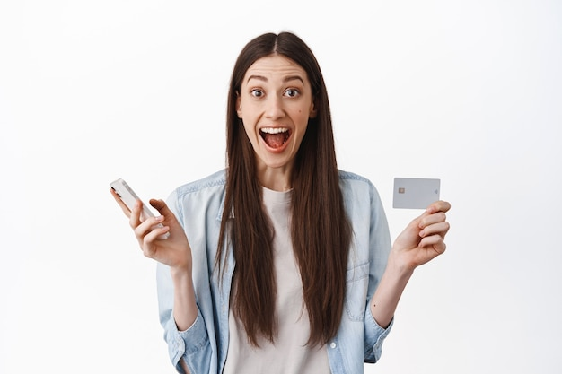 Emocionada mujer caucásica mostrando tarjeta de crédito y sosteniendo un teléfono inteligente, haciendo un pedido, esperando la entrega mientras compra en línea, de pie sobre una pared blanca