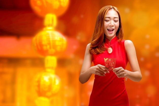 Emocionada mujer china con vestido cheongsam y sobres rojos.