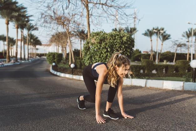 Emocionada mujer increíble motivada preparándose para correr en la calle en la mañana soleada. entrenamiento, entrenamiento, expresión de positividad, verdaderas emociones, estilo de vida saludable, trabajador