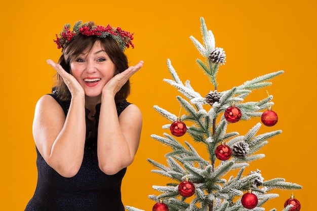 Emocionada mujer de mediana edad vistiendo corona de navidad y guirnalda de oropel alrededor del cuello de pie cerca del árbol de navidad decorado