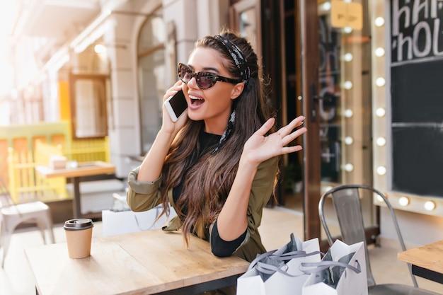 Emocionada mujer morena hablando por teléfono mientras descansa en la cafetería después de ir de compras