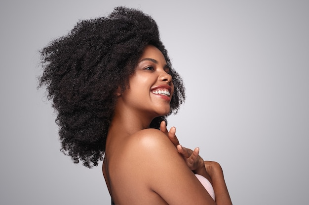 Emocionada mujer negra tocando los hombros y mirando a otro lado