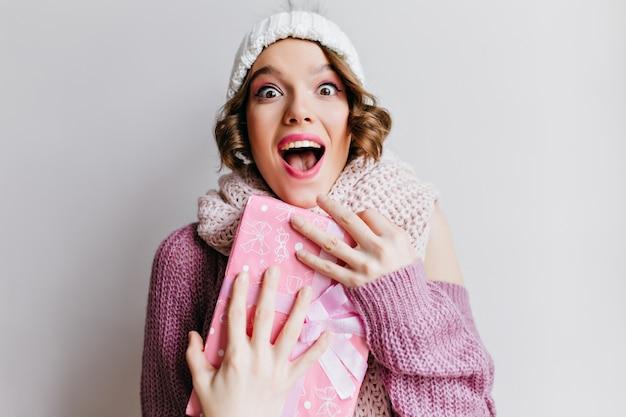 Emocionada mujer de ojos oscuros con gorro posando emocionalmente en la pared blanca. foto interior de niña hermosa sorprendida en accesorios de invierno.