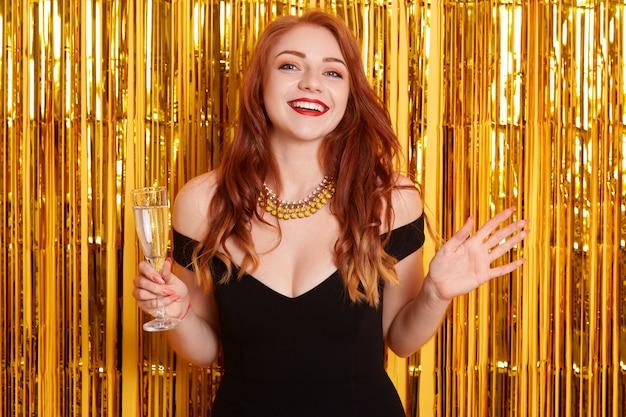 Emocionada mujer pelirroja con las manos extendidas a un lado, sosteniendo una copa de vino, celebrando el año nuevo, de pie contra la pared amarilla con brillo dorado.