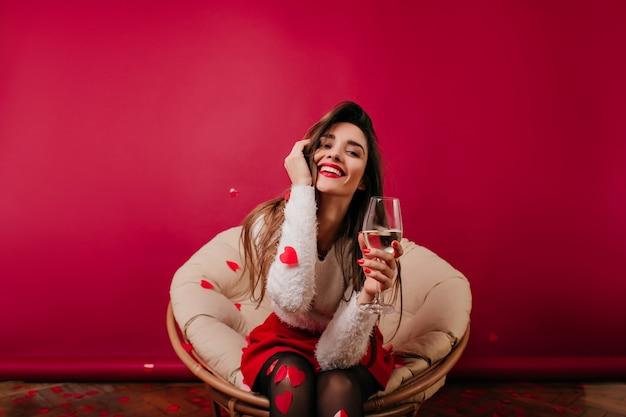 Emocionada mujer de pelo largo divirtiéndose en el día de san valentín
