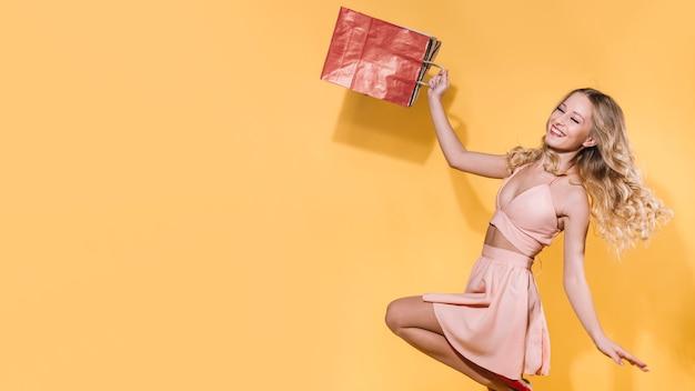Emocionada mujer saltando con bolsas de la compra.
