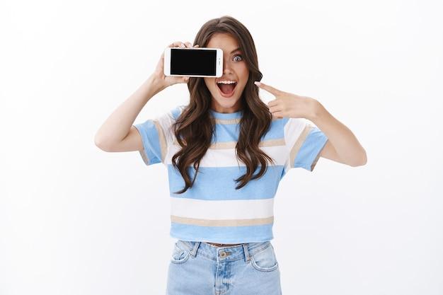 Emocionada mujer sonriente despreocupada sostenga la tapa horizontal del teléfono inteligente con un ojo con el teléfono móvil, señalando la pantalla del teléfono celular y la boca abierta fascinada, echa un vistazo a la aplicación de fotos de juegos geniales, pared blanca