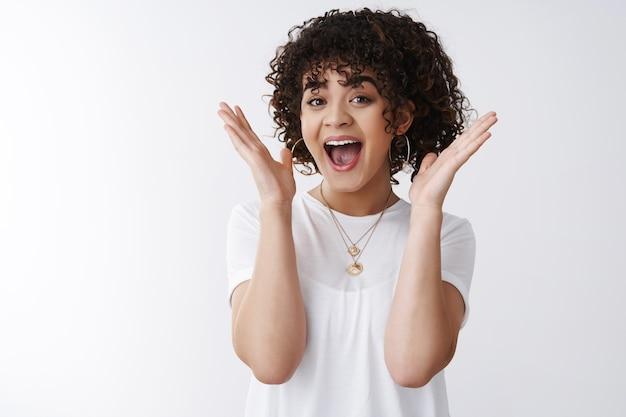 Emocionada muy feliz chica atractiva morena de pelo rizado ganando recibir buenas noticias sorprendido manos levantadas boca abierta wow sonriendo feliz reaccionando asombrado asombrado increíble suerte. fondo blanco